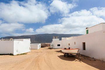 Leere Straße aus Sand mit weißen Häusern und einem Wohnwagen mit Boot in Caleta de Sebo auf der Inse von Peter de Kievith Fotografie