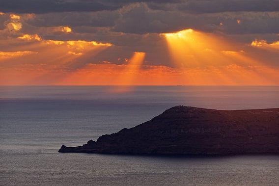 Sonnenuntergang am Meer mit Strahlen und Inselsilhouette