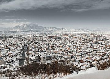 Besneeuwde stad Prizren van bovenaf in het winterseizoen van Besa Art
