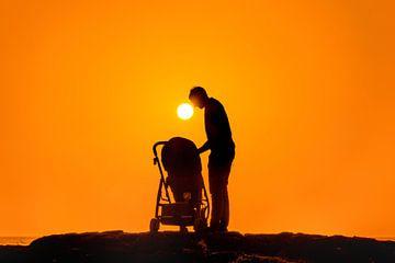 Man buigt zich over kinderwagen tijdens zonsondergang sur