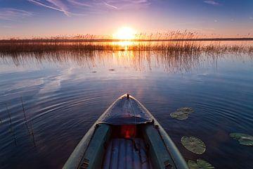 Kajak zweeft naar de opkomende zon, naar avontuurSymbol van beweging naar avontuur. van Michael Semenov