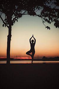 Yogapose als silhouet tijdens de ondergaande zon