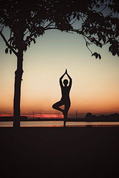 Yogapose als silhouet tijdens de ondergaande zon van Mijke Bressers