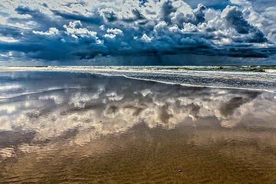 zeegezicht met spiegelende donderwolken boven de Noordzee