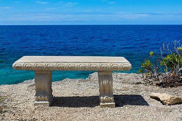 Lege betonnen bank aan kust van het eiland Bonaire met blauwe zee van Ben Schonewille
