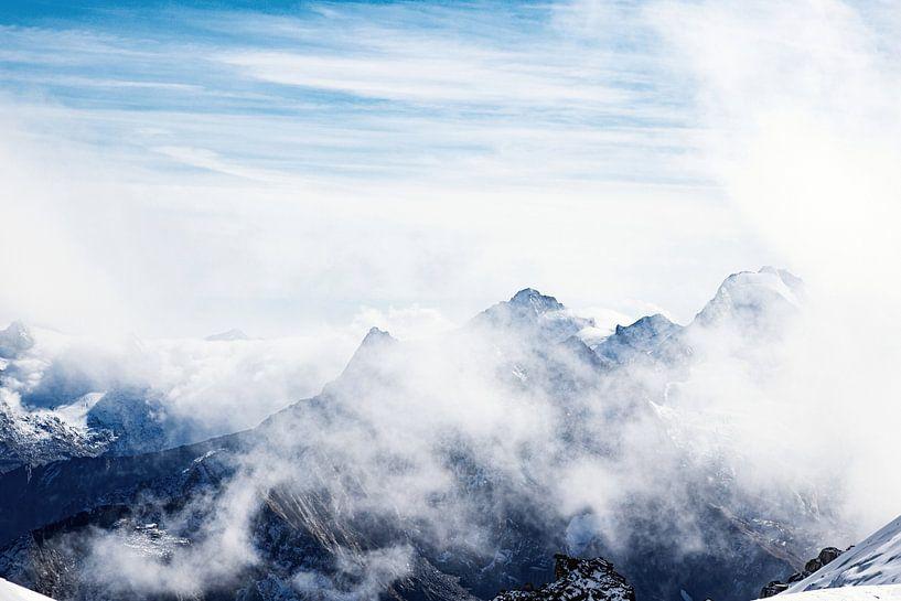 Hoge bergen steken door de wolken in de Oostenrijkse alpen van Hidde Hageman