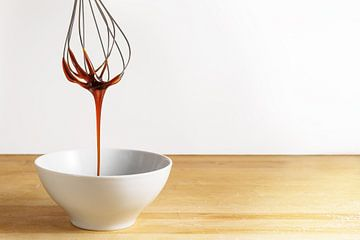 Bruine suikersiroop stroomt van een draadklopper naar een witte kom, een houten tafel en een heldere van Maren Winter