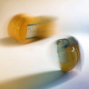 bouchons à vis jaunes en aluminium et plastique pour bouteilles en mouvement flou sur un fond clair, sur Maren Winter