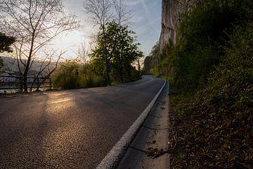 Avondlicht op verlaten weg met rotswand ernaast van FHoo