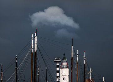 De vuurtoren van Harlingen tussen de masten en een kleine wolk erboven van Harrie Muis