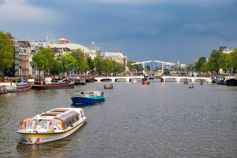De Amstel in Amsterdam met een rondvaartboot en donkere lucht van Sjoerd van der Wal