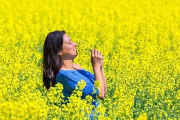 Junge kolumbianische Frau riecht gelbe Blumen in Feld mit landwirtschaftlichen Rapssamen Pflanzen von Ben Schonewille