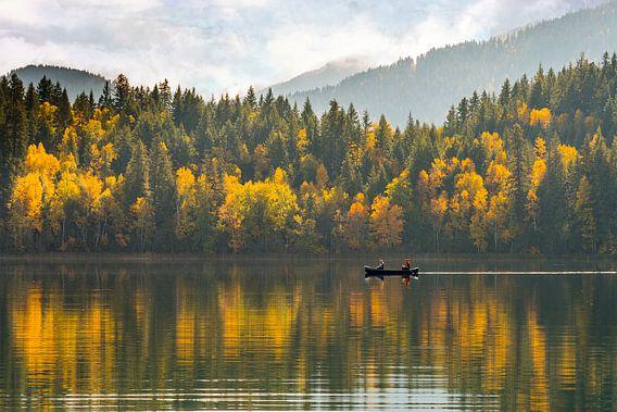 Bomen in herfstkleuren met roeiboot op spiegelend meer in Canada