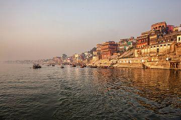 Varanasi Ganges rivier ghat met oude architecturale gebouwen en tempels gezien vanaf een boot op de  van Tjeerd Kruse