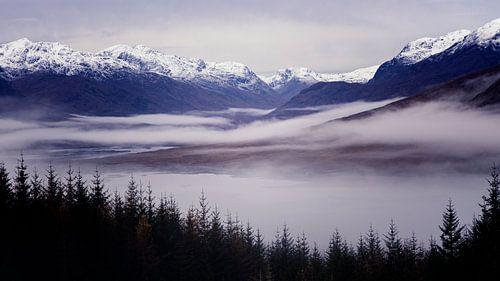 de Schotse hooglanden ontwaken op een mooie ochtend, vol mist in het dal