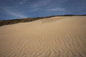 Zandvlakte met blauwe lucht