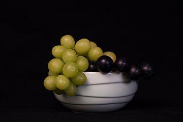 Schaal met verse witte en blauwe druiven van