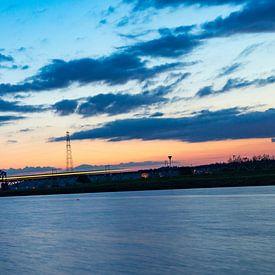 Trein snelt naar zonsondergang van Fokko Erhart
