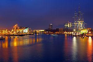 De haven van Amsterdam met het VOC schip bij nacht in Nederland van
