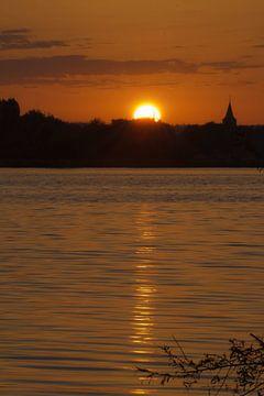 Zonsopkomst aan het water met het silhouet van een kerkje van FHoo