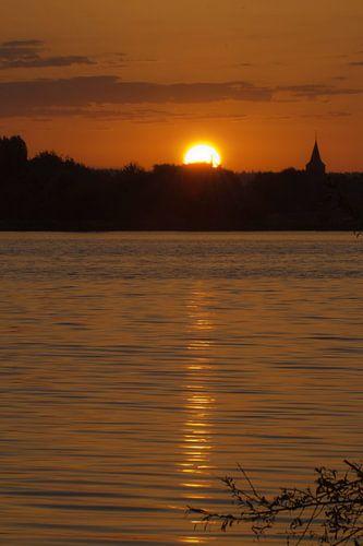 Zonsopkomst aan het water met het silhouet van een kerkje