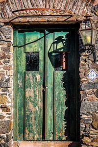 Vieille porte en bois vert avec une lanterne sur le mur
