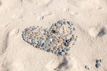 Cœur de galets sur une plage avec des traces de chiens en partie recouvertes de sable sur Hans-Jürgen Janda