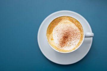Tasse Cappuccino mit Kakaopulver auf blauem Hintergrund, Ansicht direkt von oben, Kopierraum, gewähl von Maren Winter