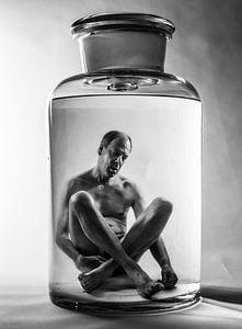 Surrealistische zwart/wit fantasiefoto van een in vloeistof geconserveerde man in een glazen pot