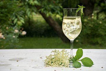 frisdrank met ijsblokjes van vlierbloesemsiroop, sap, champagne, frisdrank en munt in een glas op ee van Maren Winter