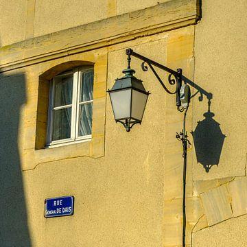 Oude lantaarn met zijn schaduw tegen warme gele muur van Petra Cremers