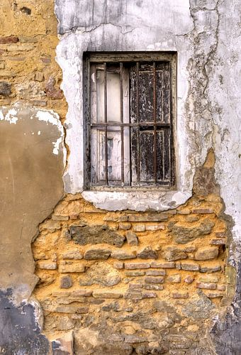 Raam in vervallen gepleisterde muur van