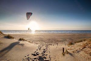 l'homme fait du parapente sur la plage au coucher du soleil en été