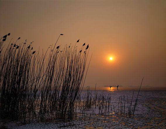 Schaatsers bij ondergaande zon