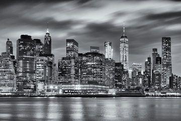 Zwart-wit foto van de skyline van Manhattan in New York, USA, in de nacht. De lichte van de wolkenkr van Bas Meelker