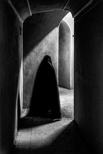 Vrouw loopt met haar schaduw door een kasteel | Iran