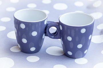 Zwei violette Kaffeebecher mit weißen Punkten auf fliederfarbenem Hintergrund mit weißen Punkten von Idema Media