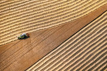 Luchtfoto van boer die graan oogst van Frans Lemmens