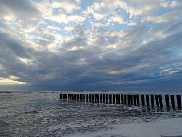 Wolkenpartij en golfbreker bij de Noordzee van Ameland van