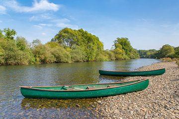 Twee kano's liggen aan de oever van Duitse rivier van Ben Schonewille