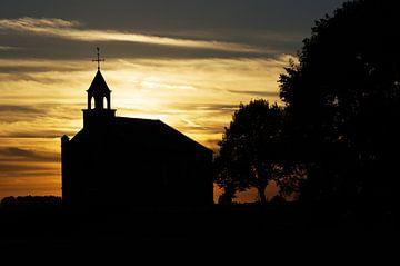 Silhouet van kerkje tijdens zonsondergang van Marcel Rommens