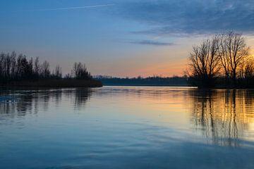 Zonsondergang over een meer met kleine eilandjes aan het eind van een winterdag van Sjoerd van der Wal