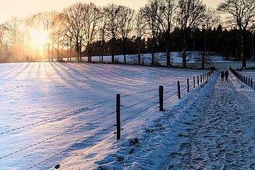 Wandelaars in sneeuwlandschap met late middagzon van Anneriek de Jong