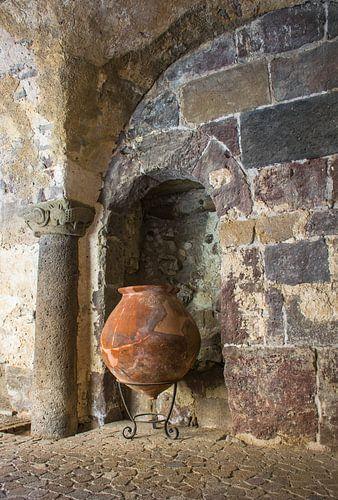 Grote kruik op standaard tegen oude muur