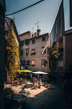 Klein steegje met café op een klein marktplein in Rovincj van Fotos by Jan Wehnert