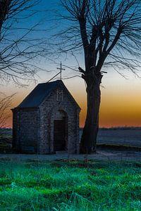 kapel midden in het weiland tijdens een kleurijke zonsondergang