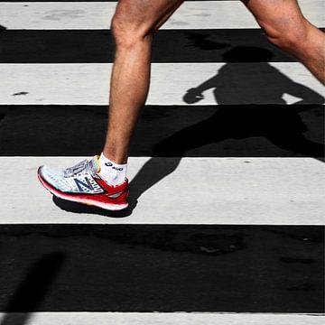Schatten eines Marathonläufers auf einem Fußgängerüberweg