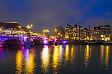 Stadsgezicht van Amsterdam bij avond met de Blauwbrug van Nisangha Masselink