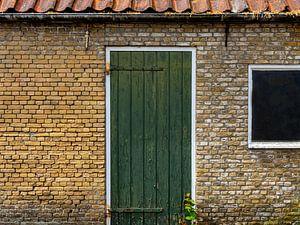 Groene deur in gebouw van oude, gele bakstenen. van