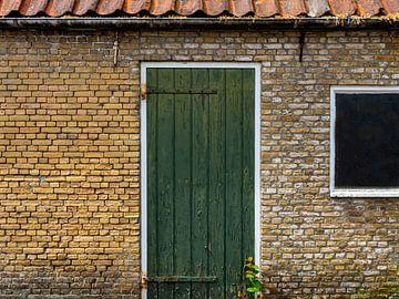 Groene deur in gebouw van oude, gele bakstenen. van René van der A